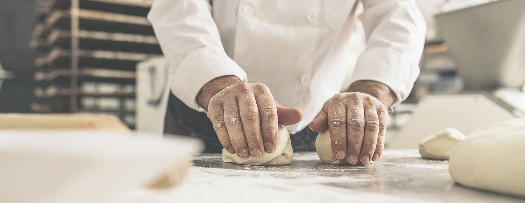 Bäcker knetet Teig.